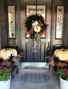 elegant Halloween decor with black and orange feathers and white pumpkins