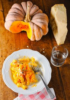Creamy Pumpkin Pasta:  ½ cup organic canned pumpkin   2 oz. nonfat Greek yogurt, plain 1 ½ tsp. extra-virgin olive oil ¼ cup chopped yellow onions or shallots ½ clove garlic or ½ teaspoon minced garlic   Dash of crushed red pepper  (optional) 1/2 tsp. pumpkin pie spice ¼ tsp. sea salt   2 tsp. Parmesan cheese, grated 2 oz. whole wheat pasta (fusilli or rotini) Optional: sprig of fresh rosemary for garnish