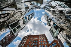   up to the sky   Gehry-Bauten Düsseldorf Das Kunst- und Medienzentrum Rheinhafen von Frank O. Gehry (USA) gliedert sich in drei kontrastreich gestaltete Gebäudeteile und wirkt wie eine riesige Skulptur. Durch die Auswahl unterschiedlicher Materialien erhält jeder Gebäudekomplex eine eigene Identität. Als Verbindung zwischen den drei Häusern wird das Material der Fassade des mittleren Baukörpers so gewählt, dass sich die Häuser auf der nördlichen und südlichen Seite darin spiegeln können.