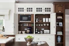This cabinet, by Humphrey Munson, creates a generous space to serve as a coffee station or storage for for small countertop appliances. Wide, bi-fold doors fold back out of the way to allow the homeowner full access to a large interior work surface. White