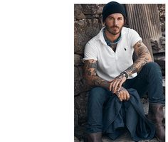 Man with tattoos sits on stone steps while wearing knit hat, a white polo shirt, jeans & moto boots Ralph Lauren iconic
