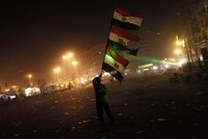An Egyptian protester waves his national flag in Cairo's Tahrir square on January 25, 2013. Protesters stormed a regional government headquarters and clashed with police as mass rallies shook Egypt on the second anniversary of a revolt that ousted Hosni Mubarak and brought Islamists to power. (Mahmoud Khaled/AFP/Getty Images) #