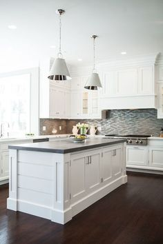 White and grey kitchen features a pair of Restoration Warehouse Altamont Metal Pendants illuminating paneled center island topped with concrete countertop.