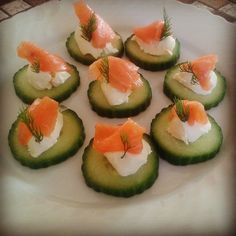 Salmon cucumber bites, so easy.  Just top cucumber slices with cream cheese then fold a slice of salmon on top followed by a branch of dill.