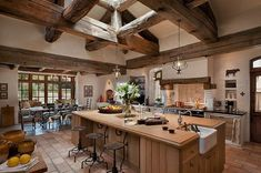 Beamed ceiling creates the rustic feel, without heavy dark wood cabinets/floors etc..  Top 10 Beautiful Rustic Kitchen Interiors For A Warm Cooking Experience