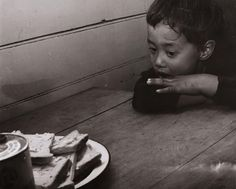 """""""Hemi Wereta is so hungry that he can hardly wait for the thick slices of bread. Maori kid"""" by Ans Westra, 1964."""