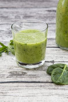 Glass bottle and glass of green smoothie made of spinach, rocket salad, apple, orange, banana and cucumber, on grey wooden table