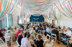 Oculux created a colourful ribbon canopy with warm lighting to transform a vast and plain function room into a more intimate wedding reception venue.