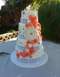 Coral and blue wedding cake with gumpaste flowers and vintage buttons