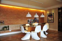 Para tornar o ambiente rústico, mas com toque urbano, foi usado tijolos no espaço. Tons amadeirados foram escolhidos para os demais elementos do ambiente. Esse revestimento aquece, e ajuda no contraponto do mobiliário moderno da sala de jantar. O projeto foi feito para um apartamento em São Paulo (SP).