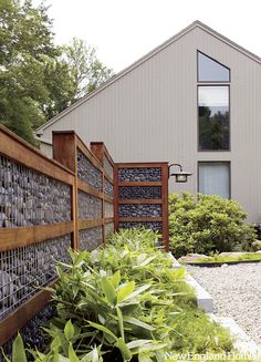 fence is a nice combination of colours with the grey infill stone and rusted steel frame with green planting in front and the white walled house behind.