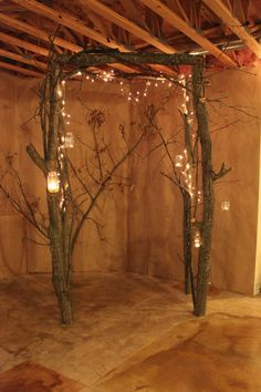 arch made from small tree trunks and branches. Used white lights and candles.