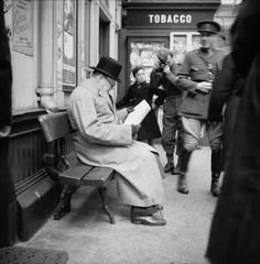 The Prime Minister Winston Churchill reads a newspaper on the platform while waiting for a train at St Andrews during a trip to Scotland to visit Polish troops, inspect coastal defences, and tour a Naval Establishment in Fife on 23 October 1940.