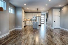 This rustic hardwood floor looks beautiful below the light whites and greys of this kitchen // Design by 303 Development Rustic Hardwood Floors, Custom Homes, Tile Floor, Kitchen Design, Lighting, Denver, King, Beautiful, Cuisine Design