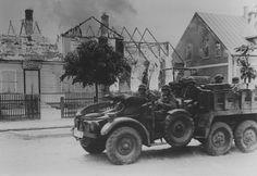 """1941, Ukraine, Un camion allemand """"Krupp-Protze"""" L2H143 Kfz.70 devant une maison en feu dans une ville de la Baltique   by ww2gallery"""