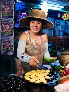 Thai woman prepares a meal at a market stall along a Lamai street in Koh Samui. Thailand.  Photo: Jon and Tina Reid via Flickr