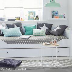 Durch neutrale Grautöne wirkt das Jugendzimmer klassisch und zeitlos. Die weiße Wandfarbe und ein weißes Bett rückt die grauen Farbakzente dezent in den…