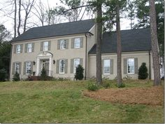 Painted taupe brick house with moss green shutters