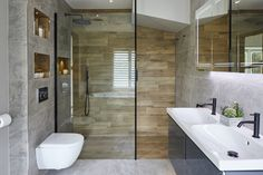 Fabulous walk in shower with dark grey sink unit, brown wood effect tiles and light grey tiles. We love the black edges round the shower screen too and the practical shelving. En-suite by Bathroom Eleven. Wood Tile Shower, Wood Bathroom, Modern Bathroom, Dark Gray Bathroom, Grey Bathrooms, Beautiful Bathrooms, Wood Effect Tiles, Shower Cubicles, Bathroom Design Luxury