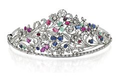 DIAMOND, RUBY, SAPPHIRE AND EMERALD TIARA, CIRCA 1925  The floral and foliate openwork frame millegrain and claw set throughout with old European, rose and old mine cut diamonds further embellished with carved and cabochon cut sapphire, ruby and emerald set buds highlighted with baguette diamonds, mounted in 14ct white gold, Austrian hallmarks