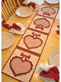 """Celebrate the month of love with this beautiful table runner!   Your kitchen decor will be complete once you deck it out with this vintage-inspired runner that features big and bold hearts hanging on a dainty bow. You can even use each individual square to make matching place mats! Finished size is approximately 12 1/2"""" x 53""""."""