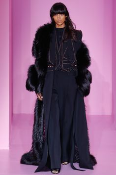 This look comes from the Givenchy Spring 2016 couture show and draws historical inspiration from 1970's fashion. The over sized fur coat was a popular trend during that time and this structured pant suit with high waisted trousers and fitted blazer are also reminiscent of retro 70's attire. 2/16/16
