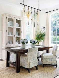 A one-of-a-kind Fortuny chandelier glows over a rustic custom table in this airy dining room. The thick, dark table anchors the room, while floral-pattern slipcovers keep dining chairs feeling lighter. Tall windows allow for