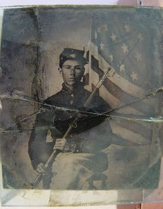 Unidentified soldier in Union uniform with bayoneted musket in front of American flag. So incredibly, incredibly young.
