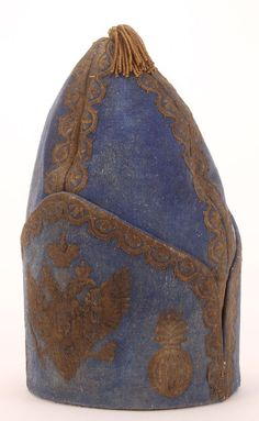 "AN EXTREMELY RARE IMPERIAL RUSSIAN HAT OF AN OFFICER IN THE DRAGOON GRENADIER REGIMENT, REIGN OF PETER THE GREAT, CIRCA 1727-1730. The ""Dutch"" bombardier cone shaped body of blue wool, ornately embroidered in silver and bullion thread, depicting on the front the Imperial Eagle flanked by flaming grenades, on the verso, a larger flaming grenade and with bullion edging on seams and bullion tassle finial."