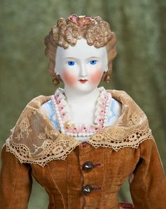 "21"" German bisque lady with brown sculpted hair and Dresden-decorated bodice ~~~21"" (53 cm.) Bisque shoulder head of lady with brown sculpted hair arranged in tight ringlet curls at sides of forehead and decorated with a pink Dresden bow and streamers, painted facial features, blue eyes, closed mouth, pierced ears, elaborate Dresden collar with white beading, new muslin body with bisque limbs, nicely costumed.  German, circa 1870."