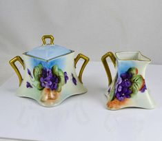Stunningly gorgeous, hand painted creamer and lidded sugar bowl. Vivid hand painted African Violets. Gold Gilt handles and trim. Made in Czechoslovakia. The stamp on the base leads to this information - Epiag Royal Made in Czechoslovakia, 1920 -1939, Stará Role Alt Rohlau(germany) Fantastic condition with very slight gold loss. Creamer measures: 3 tall x 3 1/2 wide. Sugar measures: 4 tall x 5 1/2 wide Please see all 5 pictures as they are part of the description. There is also a zo...