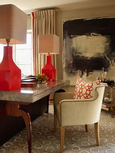 Taupe gray & red chic living room design with glossy red lamps, antique mirrored desk, ivory linen chair with French brass tacks, gray circles rug, taupe walls paint color, red circles pillow, vintage bar cart, abstract art and taupe silk drapes with red trim.