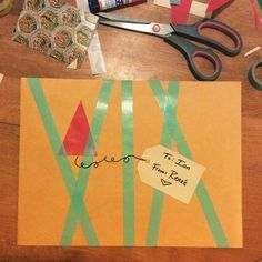 """When you don't have wrapping paper and have to improvise... [photo of a Manila envelope decorated with teal washi tape red paper cut into a triangle with a glued on tag that says """"To: Ian From: Renée"""" Craft supplies are strewn about on the table.]"""
