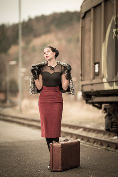 Vintage-Bloggerin RetroCat mit Cape, Vintage-Koffer, schwarzem Top und Bleistiftrock auf Reisen