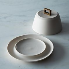 BRONZE HANDLE BUTTER DISH We love the simple, beautiful work of Portland based ceramicist Lisa Jones of Pigeon Toe. This hearty porcelain butter dish is enhanced by a square bronze handle giving it a modern but timeless elegance.
