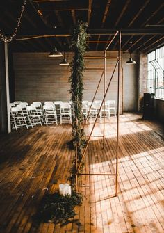 Love the industrial vibe of this gold pipe ceremony arch set against the rustic wood accents of this ceremony space | Image by Eastlyn Bright