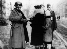 Warsaw, Poland, A German soldier inspecting the documents of a woman and her daughter
