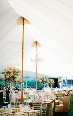 A sailcloth tent, decorated with café lighting and reclaimed wood farm tables | @krislorraine | Brides.com