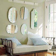a wall with multiple mirrors, all different shapes and sizes