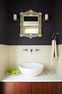If you have a bit more time and savings to invest in your bathroom makeover, adding wallpaper or a dark paint color to the upper walls and white paneling below (less pricey than retiling) will go far.    If you are considering replacing the sink, having a vintage cabinet or table fitted with a simple sink bowl can be a creative solution. While you are at it, remove that medicine cabinet and hang a pretty mirror instead.