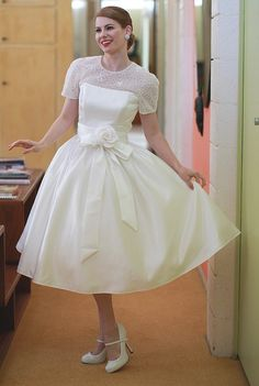Loving these Dolly Couture gowns! It was either this dress or its sister dress that was featured on the Mad Men ep of My Fair Wedding. They cropped the sleeves to a more flattering cap sleeve, and the bride looked adorable. David Tutera has me seriously considering a short gown!