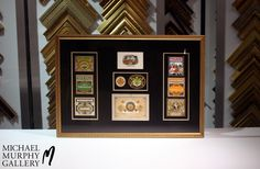 Project – Vintage Cigar Labels  Criteria – To create a design layout that compliments the cigar labels and select a frame that resembles a cigar box.  Solution – We selected an ornate gold frame with a flat profile. A double mat of metallic black and gold were chosen for contrast and to highlight the gold filigree on the cigar labels.  #FramingFriday #MMGallery