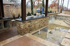 Luxury swimming pool with Ozark Mountain cobble flat thin veneer, travertine coping & outdoor bar covered structure - North Richland Hills, TX    http://www.onespecialty.com