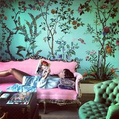Eclectic chinoiserie living room with botanical wallpaper, tufted green chair and French pink sofa
