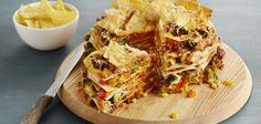 Tortillataart met nachos  4 eetlepels arachide- of olijfolie 2 winterwortels, in kleine blokjes 500 gram broccoli, in miniroosjes 2 rode paprika en 1 gele paprika 2 teentjes knoflook, fijngehakt of geperst 200 gram maïs (blik of pot), uitgelekt 2 eetlepels Mexicaanse kruiden 750 gram rundergehakt 400 milliliter gezeefde tomaten (pakje)8 tortillawraps Ø 25 cm250 milliliter (demi) crème fraîche 400 gram geraspte belegen kaas 1 grote zak tortillachips, naturel 1 potje tacosaus of hot ketchup