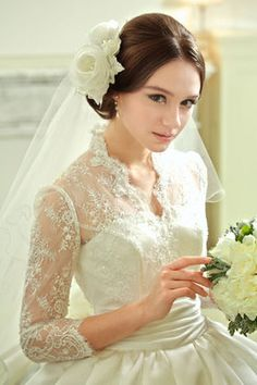 This bridal picture comes from Japan, but is not a Japanese girl. Many women of other nations work and live in modern Japan. Including many American Military women. This dress is lovely with a lace illusion bodice. Her hair is done in a fashion similar to Princess Leia, and a floral headpiece secures a rear mounted veil not designed to be worn over the face. It does flatter the design of her dress.