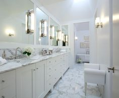 Stunning galley style bathroom with wall to wall, footed, white sink vanity accented with round, polished nickel pulls below a gray and white marble counter with a narrow marble backsplash.