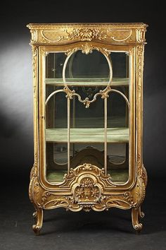 <b>ANTIQUE CONTINENTAL CARVED AND GILTWOOD VERTICAL VITRINE CABINET,</b> <i>Late 19th century.</i> The shaped rectangular top above a glass door and sides, with shell, floral and foliate decoration.