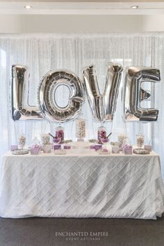 Adorned with a silver sequin backdrop and silver letter Geronimo balloons for this beautiful engagement party. White pintuck tablecloth set the base for this sophisticated and fun candy bar, with custom designed chocolate wraps and candy bar accents, with geometric elements to compliment the selection of white, silver and lilac candy. All brought together with mirrors, sequin elevations and carefully curated apothecary jars. Youtube…