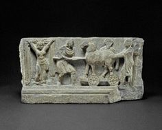 Panel showing perhaps a theme from a Trojan cycle. Almost in the centre of the space beside the doorway a horse stands on a rectangular platform with, on the outer side, two densely and irregularly spoked wheels; the horse's head, badly damaged in front, reaches almost to the top of the panel and looks slightly outwards towards the viewer. The body shows some modelling;